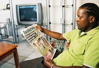An Isolezwe reader enjoying the paper at home.