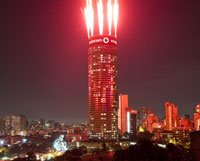 Press pack picture of Ponte City with fireworks for unveiling of Vodacom's new branding. On Friday night, 1 April 2011, only half of the Ponte LED sign was lit up. See also  by Darren Smith, which was taken on Friday night.