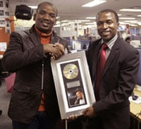 """Isolezwe editor Mazwi Xaba receives a platinum disc from gospel star Sfiso Ncwane in the newsroom. The gospel singer has won several Crown Gospel Awards in previous years and wanted to express his gratitude to the newspaper and fans for the success of his album, """"Baba Ngiyavuma""""."""
