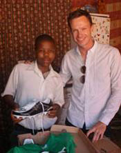 Menzi Mphambo with his new soccer boots and washing machine with Jason Levin, MD of HDI Youth Marketeers