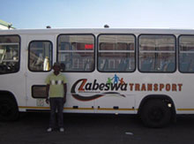 Founder of Zabeswa, Joseph Ntuli, standing proudly next to the Ubuhle bus transport - BMi Research