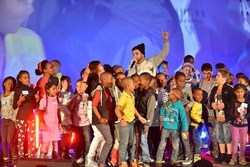 Youth performing on stage with band member, J Something from MiCasa