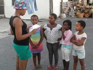 Pelokazi Vimba, a False Bay College TVET student, reading to children in her neighbourhood.