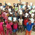 Members of the Thusanang reading club in Thusanang holding up their cut-out-and-keep storybook version of 'Where is Patch' by Wendy Hartmann.