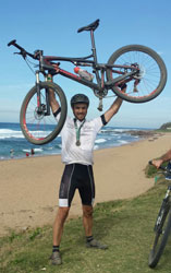 Henri Joubert, who was this the City Lodge Hotel Group's international business development manager until the end of March, raising his bike after completing the 2015 edition of the event.