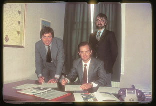 In 1982, Rowan Beattie (seated) signs the licensee agreement with Fix-a-Forms' Mike Cooper, Fix-a-Forms Manager, and Barry Denny, MD at Denny Brothers, making Pyrotec the sole distributor of Fix-a-Form booklet labels in sub-Saharan Africa.