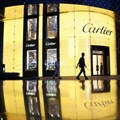 A pedestrian walks past a Cartier store, operated by Richemont, as it stands illuminated at night in Shanghai, China. Picture: