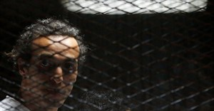 Egyptian photojournalist Mahmoud Abu Zeid, also known as Shawkan, looks on behind bars in his trial on the outskirts of Cairo, Egypt, on May 31, 2016. Shawkan was sentenced to five years in prison on September 8, 2018. Credit: Reuters/Amr Abdallah Dalsh/CPJ.