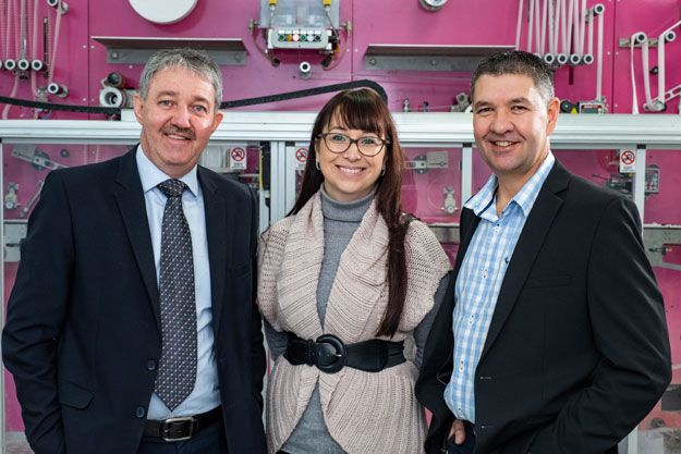 Chief executive of The Lion Match Company, Basie van Wyk (left) with Jessica Rycroft (National Marketing Manager on Personal Care, Unsgaard (middle) and George Lemon, General Works Manager for Unsgaard (right). In the background is the newly commissioned pantyliner equipment which is located at Unsgaard in Cape Town.