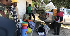 Internally displaced people offload food, blankets, and other goods after fleeing militant attacks in Naunde, northern Mozambique, on June 13, 2018. A Mozambican journalist was arrested on January 5, 2019, and held in a military prison after photographing families who fled the militant attacks. Credit: CPJ/AFP/Joaquim Nhamirre.