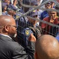 Mineral Resources Minister Gwede Mantashe talks to protesters through the locked gates of the Uitkyk Community Hall in Lutzville on Friday. Photo: John Yeld