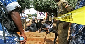 Ugandan journalists sit outside the office of the Daily Monitor, which was closed by armed police. The Monitor's website was recently ordered to suspend publication over a regulatory dispute. (Isaac Kasamani/AFP)