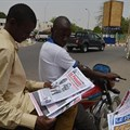 A man reads a newspaper in a street in N'Djamena, Chad, on April 12, 2016. A publisher was recently handed a suspended jail term in a defamation suit involving the president's brother. Credit: CPJ/cIssouf Sanogo/AFP.