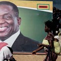 A woman walks in front of a picture of President Emmerson Mnangagwa in Bulawayo, in June 2018. Authorities in the Zimbabwean city detained documentary filmmaker Zenzele Ndebele on March 21. Credit: CPJ/AFP/Zinyange Auntony.