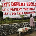 A man pushes a wheelbarrow past a sign in Liberia during the West African Ebola outbreak. AHMED JALLANZO/EPA