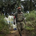 Congolese National Army solider escorts health workers to the grave of an Ebola victim, in Beni, North Kivu province. EPA-EFE/HUGH KINSELLA CUNNINGHAM