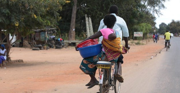 A woman and baby on a bicycle taxi in Salima, Malawi. Some Malawian men are becoming more involved in childcare. EPA-EFE