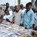 People look at front pages at a newspaper stand in Port Harcourt, after Nigeria's presidential election results were announced on February 27, 2019. Nigerian police beat two Inspiration FM journalists after covering a protest in Uyo, in Akwa-Ibom State, on September 24, 2019. Credit: CPJ/AFP/Yasuyoshi Chiba.