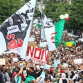 Algerian demonstrators chant and wave their country's national flag as they take part in an anti-government protest in the capital Algiers on October 15, 2019. Authorities have detained at least three more journalists in recent days. Credit: CPJ/AFP.