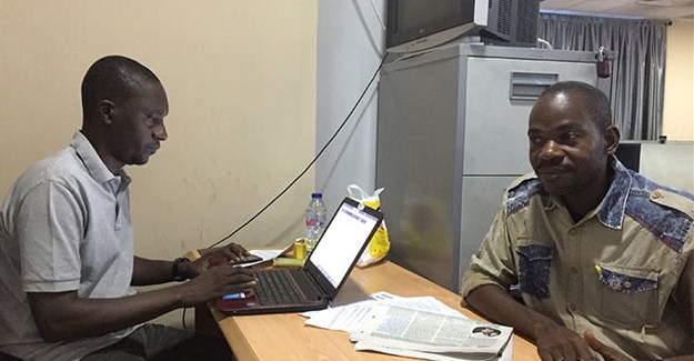 Hamza Idris (left), an editor with the Daily Trust newspaper, sits with colleague Hussaini Garba Mohammed in their office in the Nigerian capital, Abuja, in February 2019. The office was raided in January by the military, who seized 24 computers. Credit: CPJ/Jonathan Rozen.