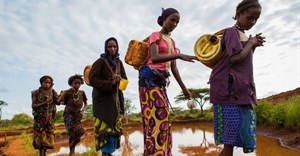 Women and girls in Gayo village, Ehtiopia collect water from a rain water pool which is purified with tablets before use. Shutterstock