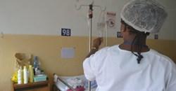 A nurse in a hospital checks an IV. Wikimedia Commons