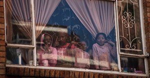 Children at window of a building in Hillbrow, Johannesburg. Children will be vulnerable if vaccinations are postponed. Photo by Marco Longari/AFP via Getty Images
