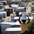 A woman carries a bucket of fresh water to an informal settlement in Khayelitsha, near Cape Town. South Africa has the widest wealth gap in the world. Photo by RODGER BOSCH/AFP via Getty Images