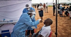 A healthcare worker collecting a swab for a Covid-19 test from a community member. AFP via Getty Images