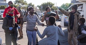 Land occupiers in Observatory, Cape Town, sing struggle songs while law enforcement officers hand out fines to them for contravening by-laws on Wednesday morning. Photo: Ashraf Hendricks / GroundUp