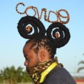 "Hair stylist Onele Cembi twists his dreadlocks into the words ""Covid-19"". Photo: Thamsanqa Mbovane"