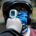 A security guard checks the body temperature of a motorcyclist as a preventive measure. Risa Krisadhi/SOPA Images/LightRocket via Getty Images