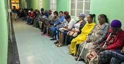 Queue of seated outpatients, waiting patiently inside a provincial hospital corridor in Port Elizabeth. Shutterstock