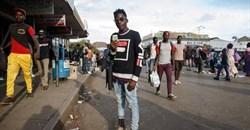 Artist Kudakwashe Chigodo poses for a portrait with his smartphone in Harare. Jekesai Njikizana/AFP/Getty Images.