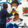 Congolese artist Chris Shongo paints on the outside wall of the Academie des Beaux-Arts in Kinshasa on June 18, 2020.