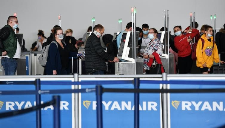 Passengers queue up to check in for flights at Stansted Airport London, Britain, July 2020. Andy Rain/EPA-EFE