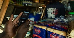 A man makes a payment from his mobile phone for basic food items including bread at a local tuck shop in Epworth, on the outskirts of Harare. Photo by Jekesai Njikizana/AFP via Getty Images