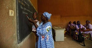 A teacher holds a child as young women learn business skills at Centre D'Apprentissage Feminin (C.A.FE.) in Bamako, Mali, Africa in June 2018. The school is funded by the Canadian NGO Education internationale, a co-operative offering exchange and development services in education. THE CANADIAN PRESS/ Sean Kilpatrick