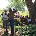 Mosadi Kwele speaks at a community meeting held on 19 January 2020, while Itumeleng Nyaka holds the megaphone. Like many others at the meeting, Kwele says Ikwezi Vanadium must respond to the community's queries before continuing with mining activities at Haakdoornfontein farm. Photo: Masego Mafata