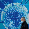 FILE PHOTO: A man wearing a protective face mask walks past an illustration of a virus outside a regional science centre amid the coronavirus disease (Covid-19) outbreak, in Oldham, Britain August 3, 2020. REUTERS/Phil Noble/File Photo
