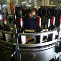 A worker checks bottles of wine coming out of a production line at Nederburg Wine Estate in Paarl, South Africa, 8 July 2020. Reuters/Mike Hutchings