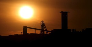 The sun sets behind a shaft outside the mining town of Carletonville, west of Johannesburg, file. Reuters/Siphiwe Sibeko