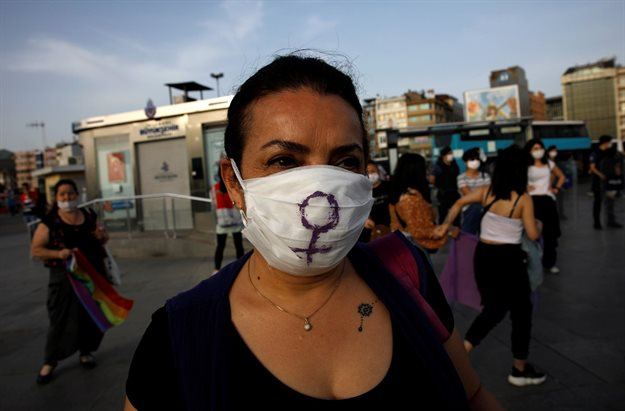 A woman wears a protective face mask as demonstrators keep social distance by holding onto purple ribbons as they protest for women rights and against child abuse, amid the spread of the coronavirus disease (Covid-19), in Istanbul, Turkey, 20 May 2020. Reuters/Umit Bektas