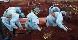 Funeral workers wearing personal protective equipment carry a casket during the burial of a Covid-19 victim, amid a nationwide coronavirus disease (Covid-19) lockdown, at the Olifantsvlei cemetery, south-west of Joburg, South Africa 6 January, 2021. Reuters/Siphiwe Sibeko