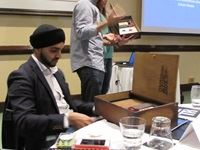 Tej Rekhi (Sizmek - UK) opening his Tuongee gift, while the creative agency behind the design and creation if the gifting (Milk Is Good) takes guests through it