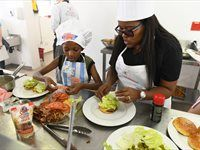 Contestants Tshegofatso Motsei and 9-year old Gogontle preparing their Gourmet Burgers