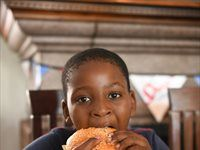 Spur Secret Tribe member enjoying his Gourmet Burger creation at Prue Leith Chef's Academy
